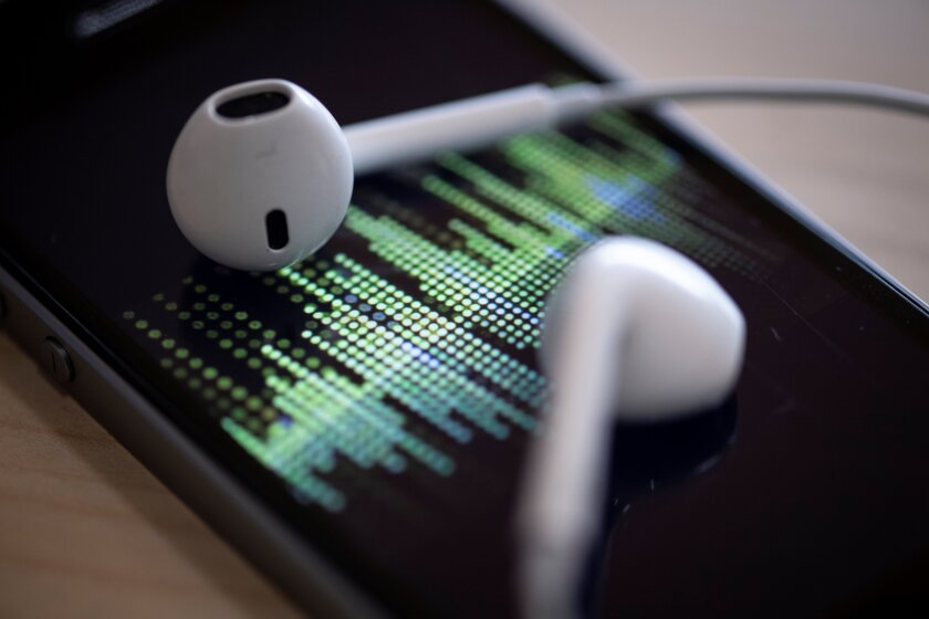 Closeup of earphones lying on a smartphone as an audio podcast is played.