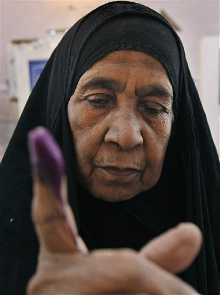 Zahiya Kadim, who is blind, displays her inked finger after casting her vote in Basra, Iraq, Sunday, March 7, 2010. Under a blanket of tight security designed to thwart insurgents attacks, Iraqis went to the polls on foot Sunday in an election testing the ability of the country's still-fragile democracy to move forward at a time of uncertainty over a looming U.S. troop drawdown and still jagged sectarian divisions. (AP Photo/Nabil al-Jurani)