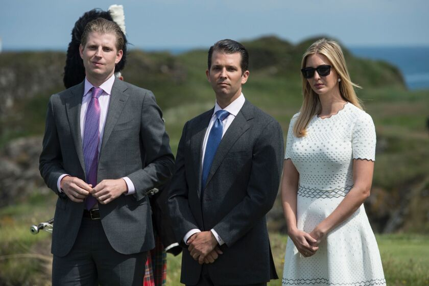 From left, Eric, Donald Jr. and Ivanka Trump in a field in Turnberry, Scotland.