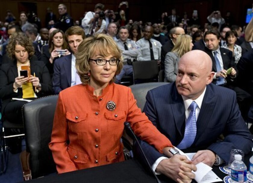 FILE - In this Jan. 30, 2013 file photo, former former U.S. Rep. Gabrielle Giffords, who survived a gunshot to the head in 2011, during a mass shooting in Tucson, Ariz., sits ready with her husband, retired astronaut Mark Kelly, at a Senate Judiciary Committee hearing on Capitol Hill in Washington to discuss legislation to curb gun violence. Giffords and Kelly are scheduled to be in Denver, Monday, March 4, 2013 to testify in support of at least one of the seven gun-control bills being consider