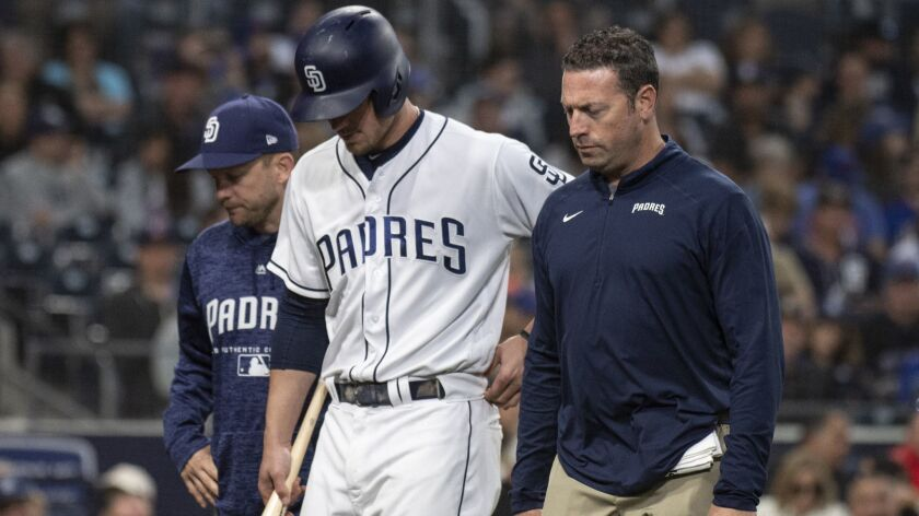 San Diego Padres' Wil Myers, center, exits with an injury during the fifth inning of a baseball game
