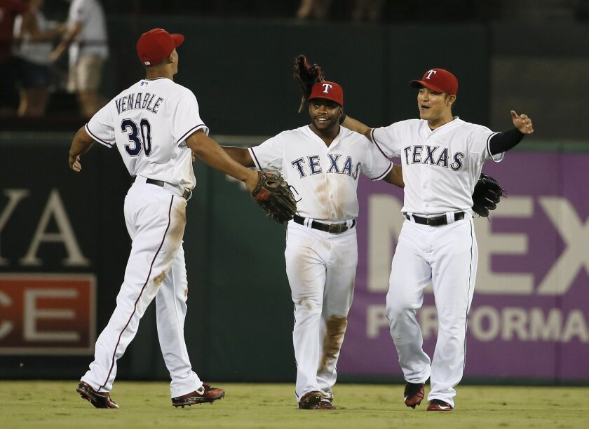 The Rangers' Will Venable (30), Delino DeShields and Shin-Soo Choo, right, of South Korea, celebrate their 4-1 win over the Baltimore Orioles in baseball game Friday, Aug. 28, 2015, in Arlington, Texas.