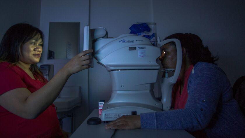 A flash of light illuminates the eye of Juana Lorez, right, as Bea Tomayo photographs her retina at Los Angeles County-USC Medical Center.