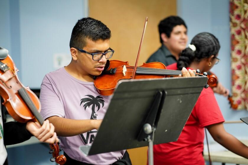 Roberto Reyes playing viola at OCCTAC with Jairo Mendez and Lupita Marcial.