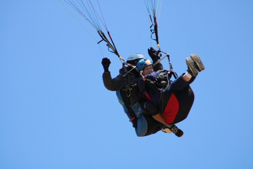 Wanda Parrent, 90, paraglides over friends and family for her birthday.