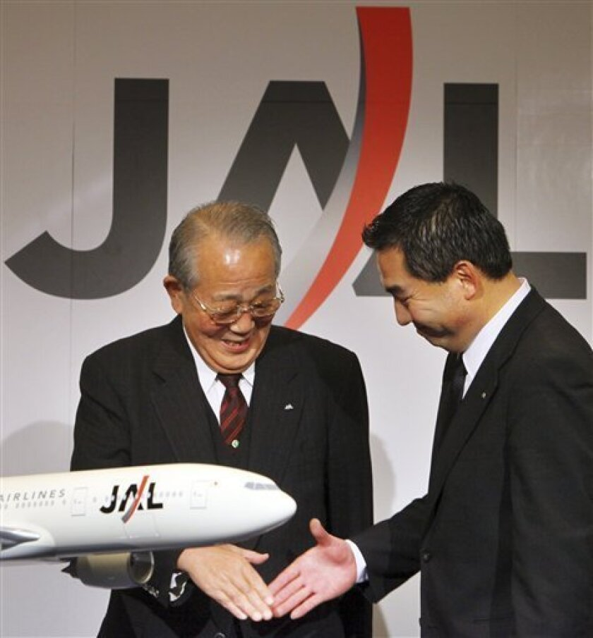 "Japan Airlines' new chairman Kazuo Inamori, left, and new President Masaru Onishi shake hands following their press conference in Tokyo Monday, Feb. 1, 2010. Onishi said Monday the carrier will decide on its alliance partner ""as soon as possible"" but wouldn't provide a timeframe for a decision on sticking with American Airlines or shifting to Delta. (AP Photo/Junji Kurokawa)"