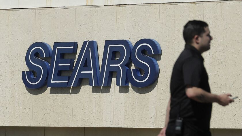FILE- In this March 28, 2018, file photo, a man walks in front of a Sears sign in San Bruno, Calif.