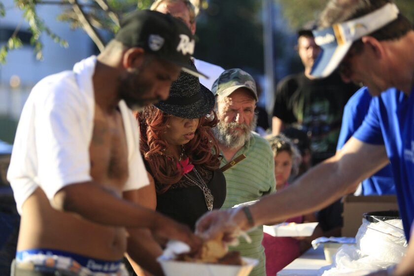 Renee Mathis (center, in black hat) receives food provided by The Dream Center San Diego outside International Love Ministries of God on 16th Street on Monday. The group is one of many that feed hundreds of needy people in downtown San Diego every day.