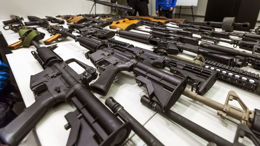 "A variety of military-style semi-automatic rifles obtained during a buyback program are displayed at Los Angeles police headquarters. Owners of semi-automatic guns with ""bullet buttons"" were required to register them with the state by the end of June."