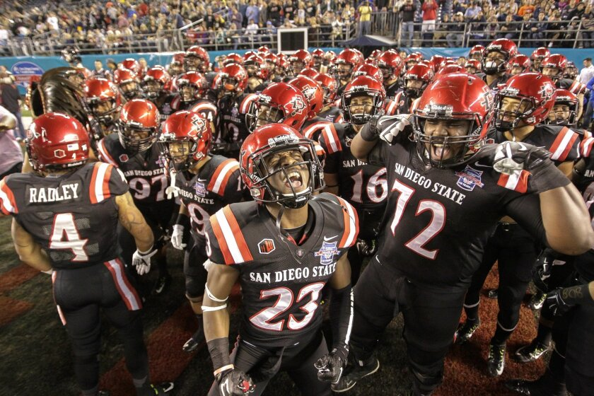 San Diego State offensive lineman Darrell Greene, #72, gets pumped with his Aztecs teammates as they come on to the field before the start of their game against Navy last year in the San Diego Credit Union Poinsettia Bowl at Qualcomm Stadium in San Diego.