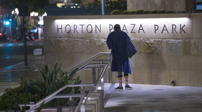 SAN DIEGO, CA 1/25/2019: A homeless man walks past the Horton Plaza Park sign before sunrise, during the annual homeless count. Jimbo's alleges that the mall's new owner, Stockdale Capital Partners, has allowed the center to further deteriorate.