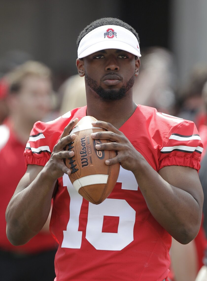 FILE - In this April 18, 2015, file photo, Ohio State quarterback J.T. Barrett is shown during Ohio State's NCAA college football Spring game in Columbus, Ohio. Ohio. Ohio State quarterback J.T. Barrett has been suspended for one game after being cited with a misdemeanor offense of operating a vehi