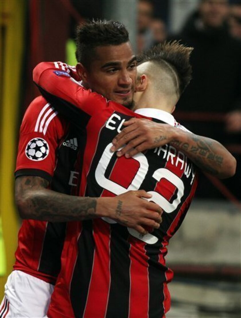 AC Milan's Kevin-Prince Boateng, left, is hugged by teammate Stephan El Shaarawy, after scoring during theirChampions League round of 16, first leg soccer match against Barcelona, at the San Siro stadium in Milan, Italy, Wednesday, Feb. 20, 2013. (AP Photo/Felice Calabro')