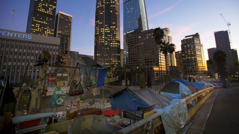 The city lights are coming on at dusk, as the sun goes down over Los Angeles. A row of tents in a ho