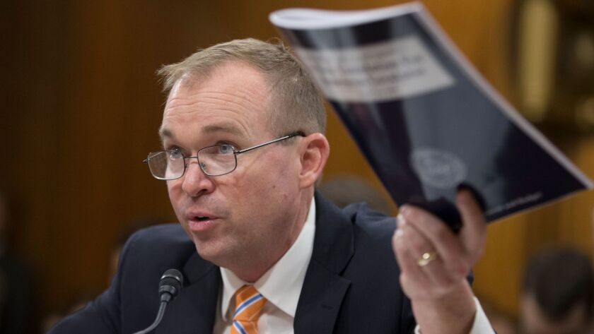 epa05989545 Office of Management and Budget (OMB) Director Mick Mulvaney holds a copy of the Preside