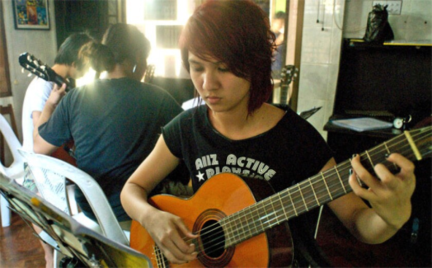 SUBVERSIVE? Honnay Lwin Loin practices at a Yangon music school whose U.S. funding lures the government snoops.