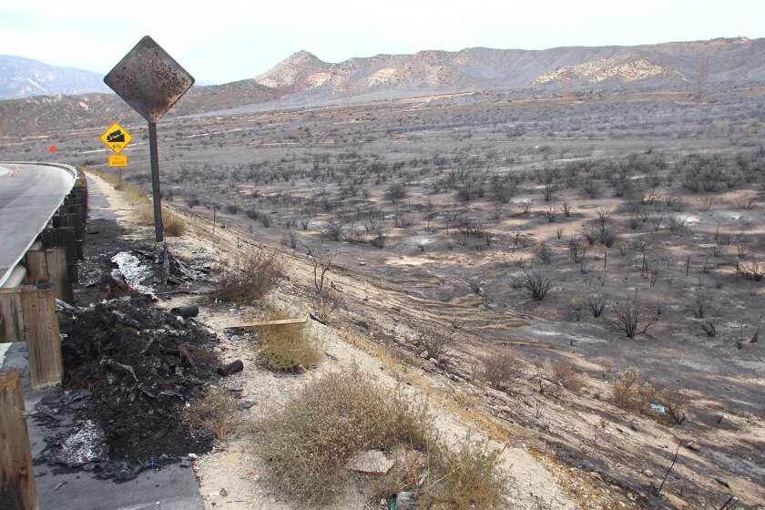 Burned terrain is seen on the reopened southbound side of Interstate 15, the main connector between Southern California and Las Vegas in the Cajon Pass, Calif., on Saturday, July 18, 2015. The fire swept across Interstate 15 on Friday, destroying the vehicles before burning three homes and 44 more vehicles in the community of Baldy Mesa. It has blackened 5.5 square miles. (AP Photo/Matt Hartman)