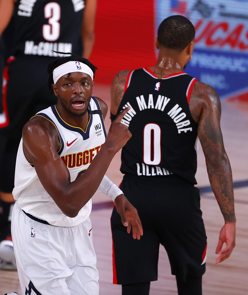 Denver Nuggets' Jerami Grant, left, reacts to his slam dunk during the third quarter of an NBA basketball game against the Portland Trail Blazers, Thursday, Aug. 6, 2020, in Lake Buena Vista, Fla. (Kevin C. Cox/Pool Photo via AP)