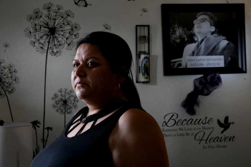 A woman in a home with a picture of her missing son on a wall behind her.