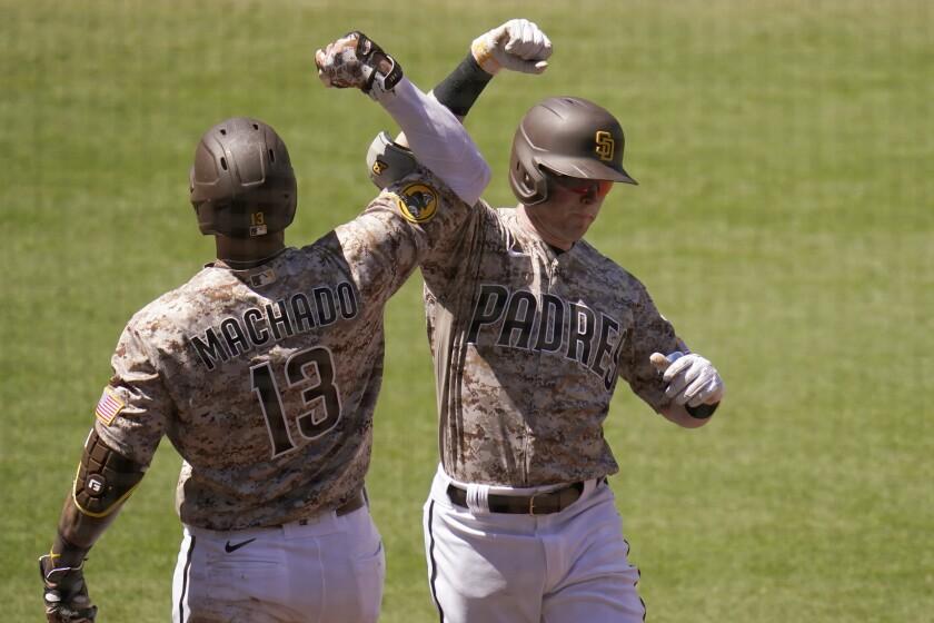 Jake Cronenworth, de los Padres de San Diego, es felicitado por su compañero Manny Machado