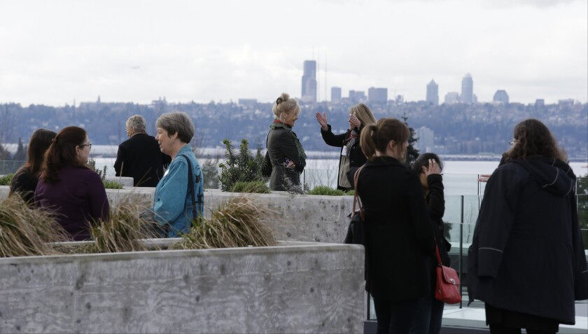 Workers and visitors gather on a roof deck of a new Google building in view of downtown Seattle buil