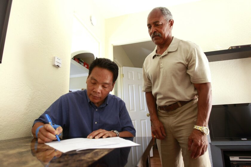 James DeGuzman, a veteran helped by the Housing Our Heroes program, signs a rental document on July 21, 2016 as landlord Noble Robinson looks on. / photo by Hayne Palmour IV * U-T