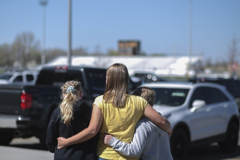 People embrace outside after a shooting at Rigby Middle School in Rigby, Idaho on Thursday, May 6, 2021. Authorities say a shooting at the eastern Idaho middle school has injured two students and a custodian, and a female student has been taken into custody. (John Roark /The Idaho Post-Register via AP)