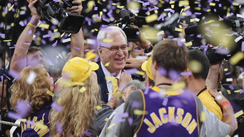 Phil Jackson celebrates with fans after the Lakers defeated the Boston Celtics to win the NBA title in 2010.
