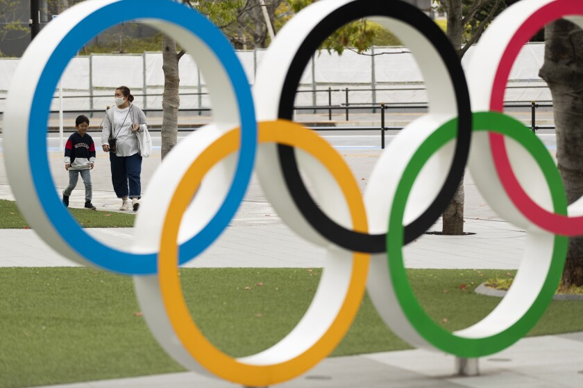 A mother and a boy walk by a display of the Olympic rings at the Japan Olympic Museum in Tokyo on Friday, April 2, 2021. Reports in Japan on Tuesday, April 6, 2021, said Tokyo Olympic organizers have canceled a water polo test event set for this weekend. The reports said technical officials were unable to go to Japan because of strict procedures to enter the country. (AP Photo/Hiro Komae)