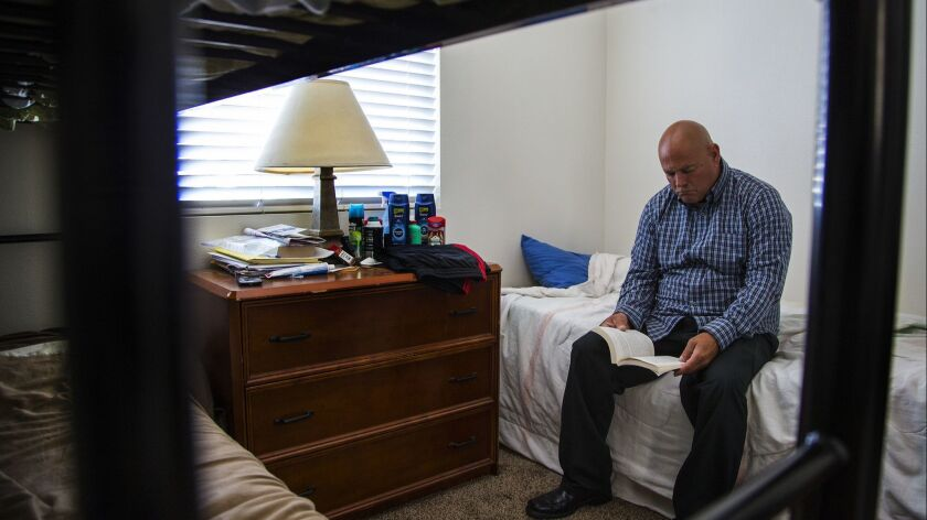 HESPERIA, CA - JUNE 2, 2016: Michael Brown,46, spends time reading in his room at Hollister House, a