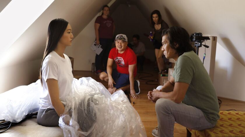 "Tiffany Chu, left, and Tohoru Masamune rehearse a scene for the show, ""Artificial,"" which streams on the platform Twitch. Filming took place in a Hollywood Hills home, where director and co-creator, Bernie Su, center, watches."