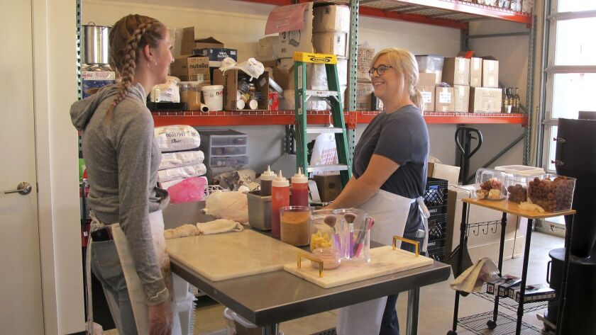 Craft doughnut shop owner Amy Pruchnic, right, talks with an employee at her busy new store in downtown Spokane, Wash, on June 8. The state's second-largest city is booming these days.