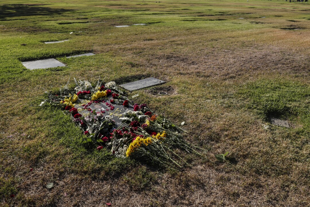 Flowers are arranged on a gravestone in the grass