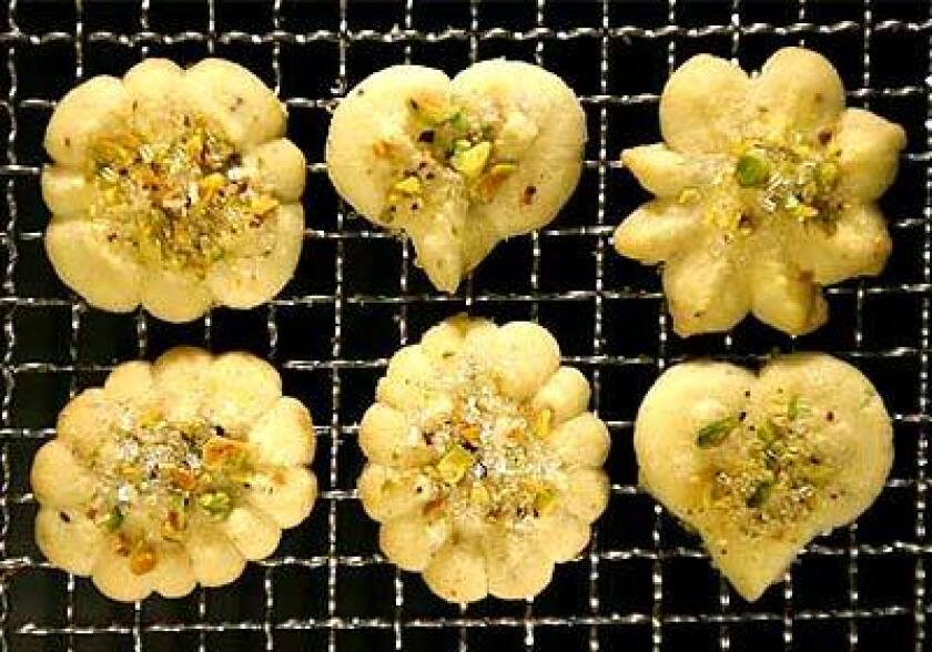 In butter spritz cookies, the cardamom complements the crushed pistachios and the big sugar crystals sprinkled on top. The cookie press, equipped with metal disks of a various shapes, can speed holiday baking by pumping out a dozen cookies in a minute.