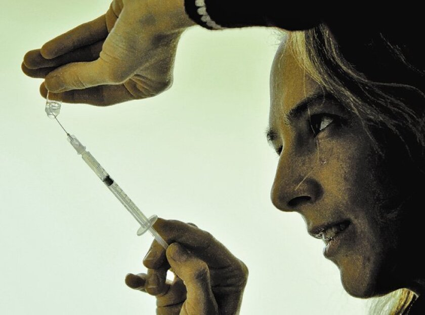 A doctor absorbs the Hungarian made Fluval-P, H1N1 vaccine from a vial in Budapest, Hungary.