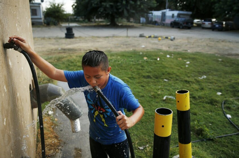 In this Monday, Sept. 14, 2015 photo, 9-year-old Carlos Velasquez drinks well water from a hose at a trailer park near Fresno, Calif. Residents of the trailer park receive notices warning that their well water contains uranium at a level considered unsafe by federal and state standards. (AP Photo/J