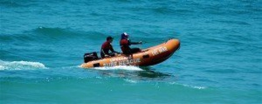 Tomas Bryant and Tyler Grant pilot an inflatable rescue boat on calm surf.