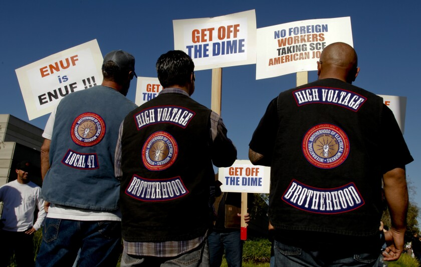 """Wearing their """"High Voltage"""" union vests, some of the more than 500 members of the International Brotherhood of Electrical Workers (IBEW) walk the picket line in front of the Southern California Edison building in Irvine on Feb. 10. The IBEW is supporting the hundreds of IT workers who Edison is laying off in favor of workers in India."""