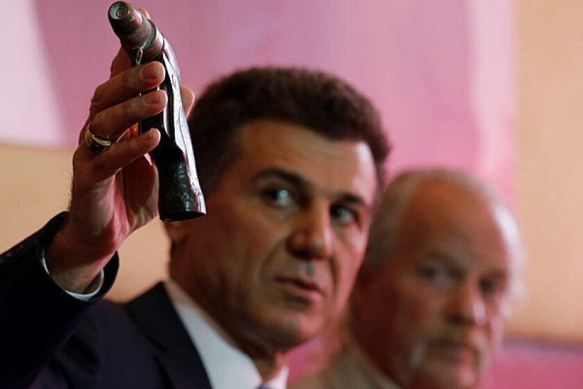Attorney Garo Mardirossian last year holds up the water nozzle that Long Beach Police officers mistook for a gun when they shot and killed Doglas Zerby, 35, whose father, Mark Zerby, is at right.