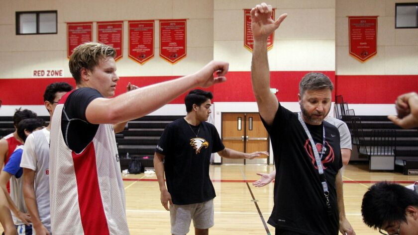 Escondido Adventist basketball coach Bill Davis (right) counts on his son — Ethan Davis (left) — for points, rebounds and leadership.
