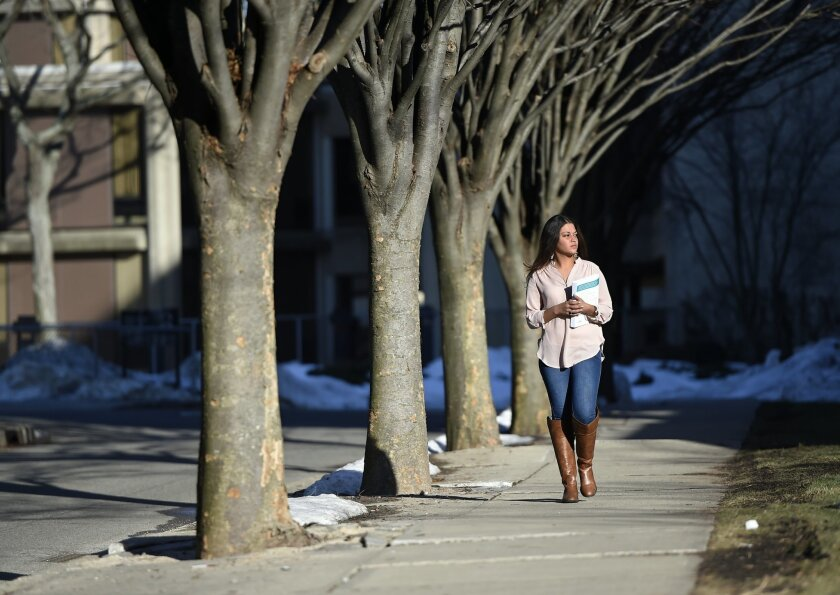 In this Feb. 2, 2016 photo, Naila Amin, 26, walks through the campus of Nassau Community College where she is a student in Garden City, N.Y. Amin, who was forced into marriage at the age of 15 to a 28-year-old cousin in Pakistan who beat and mistreated her, aspires to become a social worker and ope
