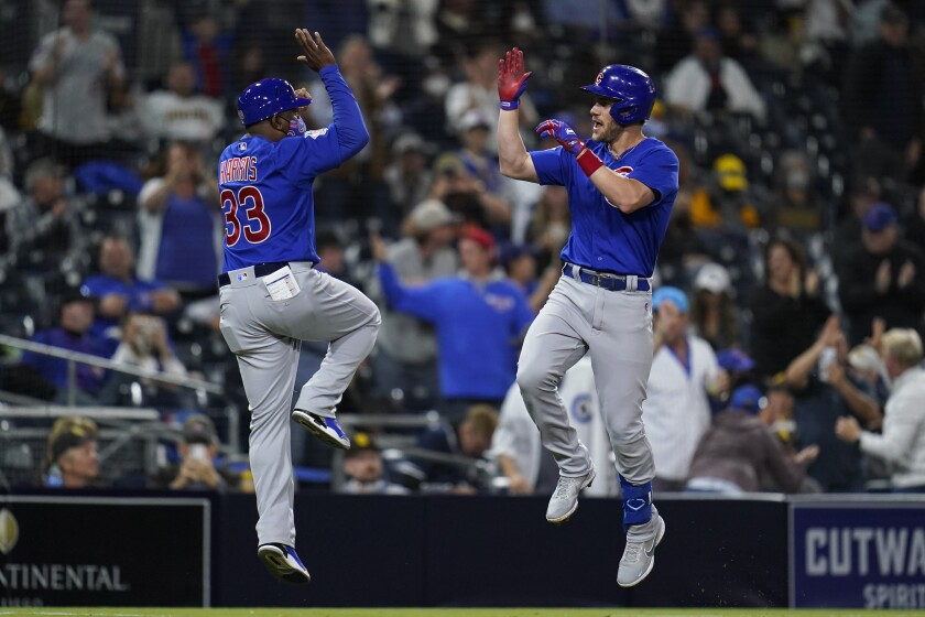 Chicago Cubs' Patrick Wisdom, right, celebrates with third base coach Willie Harris after hitting a two-run home run during the sixth inning of the team's baseball game against the San Diego Padres, Tuesday, June 8, 2021, in San Diego. (AP Photo/Gregory Bull)