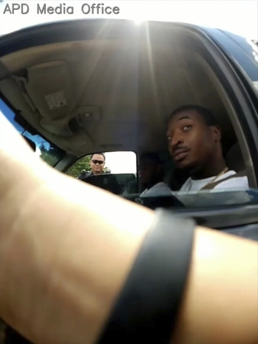"""FILE - This Sept. 1, 2018 image from police body camera video provided by the Arlington, Texas, Police Department, shows an officer, foreground, talking to O'Shae Terry after stopping him for a vehicle registration violation, in Arlington, as a second officer, Bau Tran, background left, looks in from the passenger side window. Prosecutors say Tran, charged in the fatal shooting of Terry during a traffic stop last year had a disciplinary record with his department that showed """"bad character."""" (Arlington Police Department via AP, File)"""
