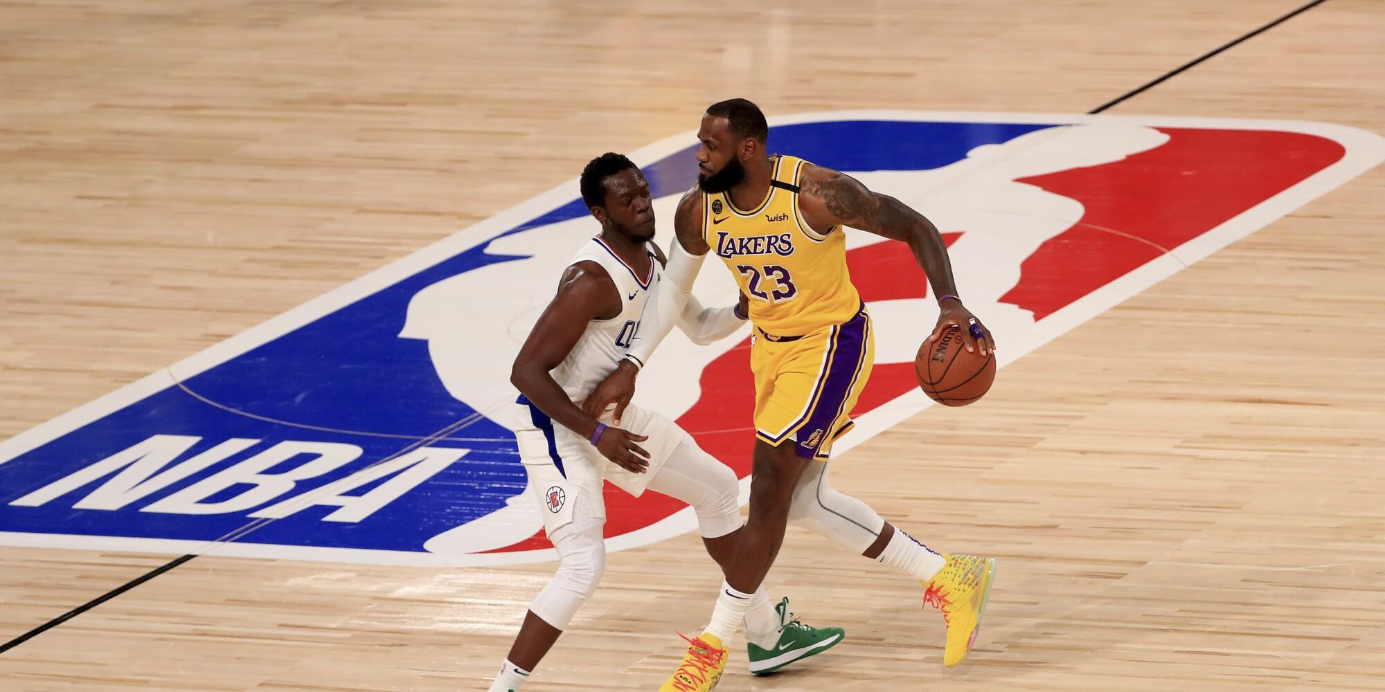 LeBron James brings the ball up court against Reggie Jackson.