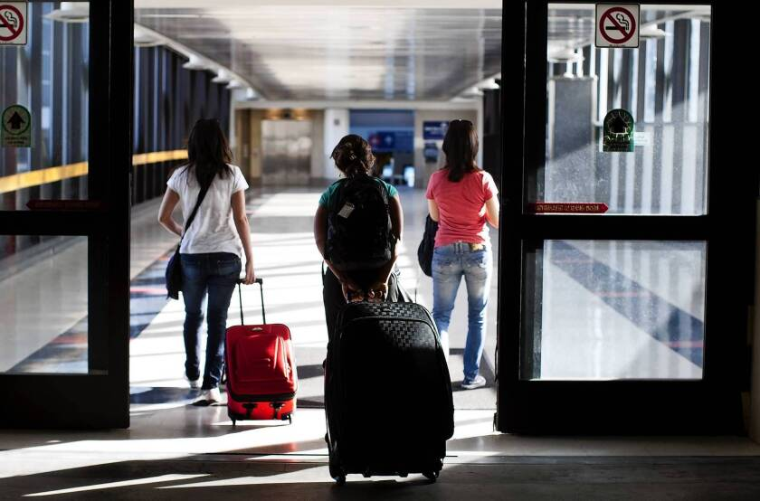 A survey by Capital One found 52% of those who plan to travel this summer expect to use credit card reward points to cover costs, up from 42% a year ago. Above, travelers at LAX.