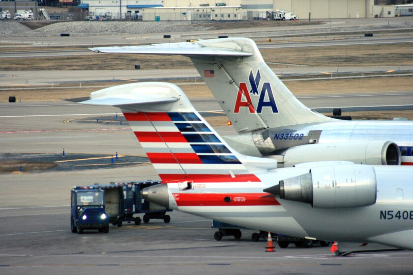 Two American Airlines jets are serviced at the St. Louis airport in December. American reported record profit for the second quarter of 2014.