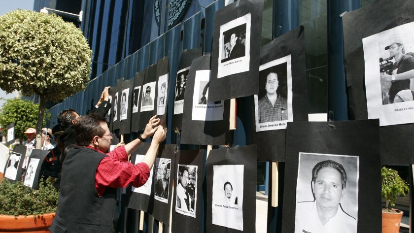 An man hangs photos of slain journalists during a protest at the gates of the Attorney General's Off