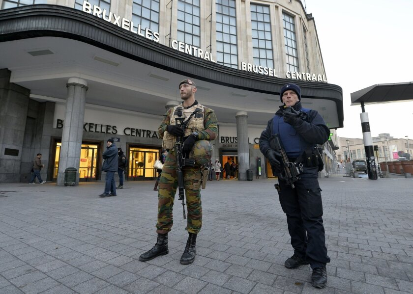 A Belgian policeman and a soldier stand guard outside the central station in Brussels on Monday.
