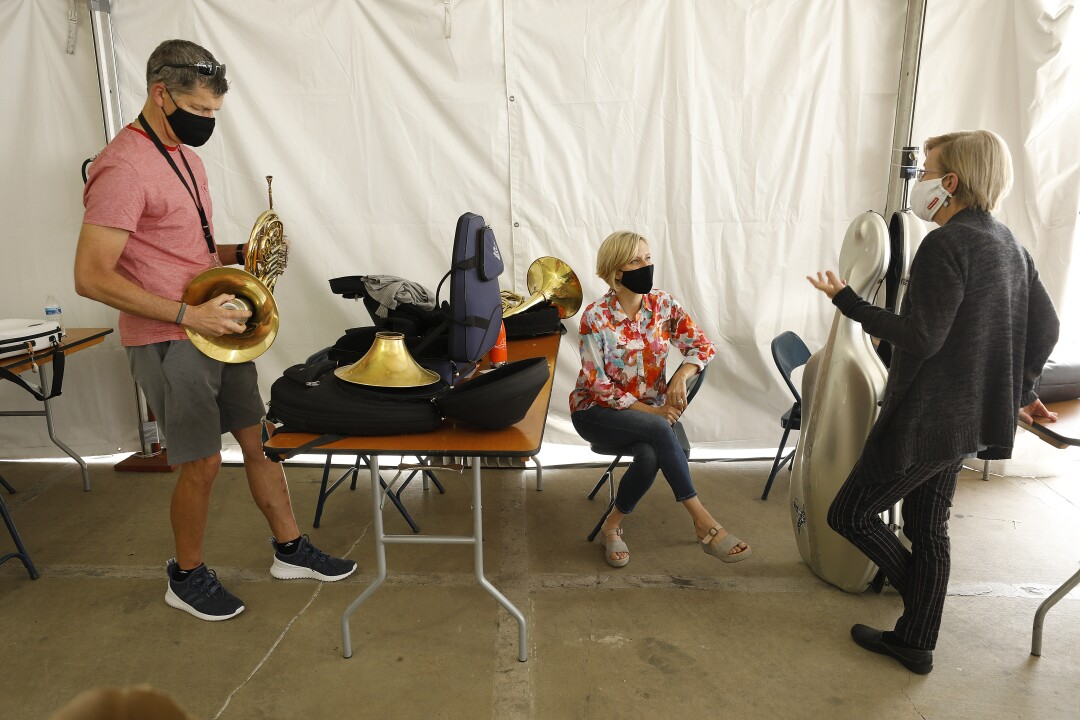 Musicians in masks converse among their instruments