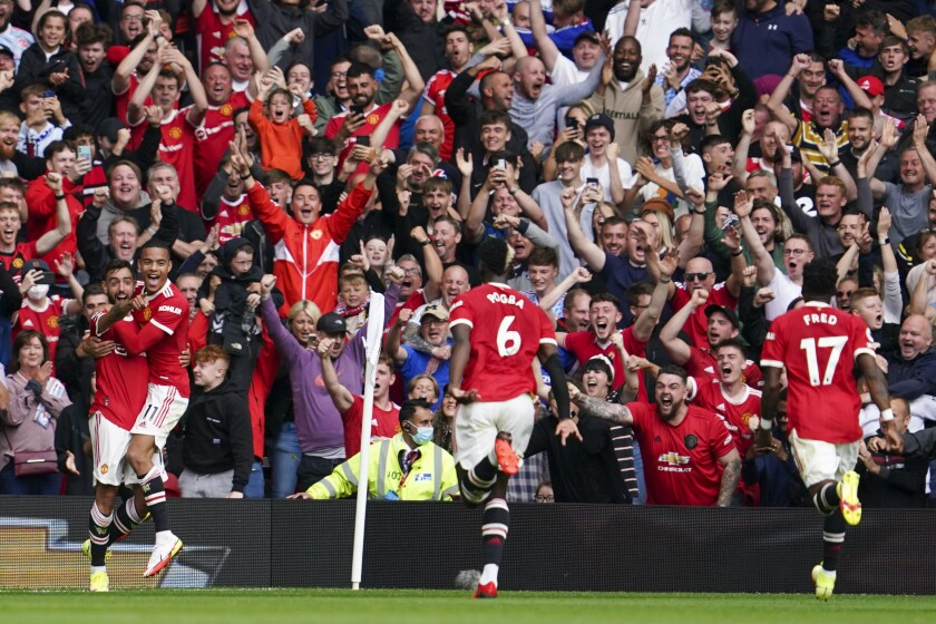Manchester United's Bruno Fernandes, left, celebrates with teammates after scoring his team's first goal during the English Premier League soccer match between Manchester United and Leeds United at Old Trafford in Manchester, England, Saturday, Aug. 14, 2021. (AP Photo/Jon Super)